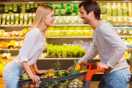 Finding joy in the simplest things. Cheerful young couple leaning at the shopping cart and looking at each other while shopping in a food store Stock Photo