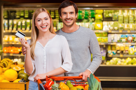 We like shopping together. Cheerful young couple smiling at camera and showing a credit card while standing in a food store