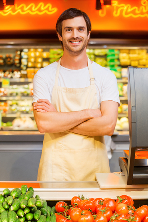 supermarket checkout: How may I help you? Handsome young cashier keeping arms crossed and smiling while standing at supermarket checkout