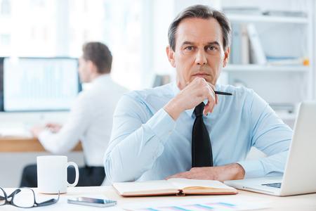 liderazgo empresarial: La cara del hombre de negocios leadership.Thoughtful plenaria en la tenencia formalwear mano en la barbilla mientras se está sentado en su lugar de trabajo Foto de archivo