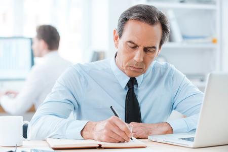 persona escribiendo: Poner sus ideas sobre el papel. Hombre de negocios serio por escrito Formal en bloc de notas mientras est� sentado en su lugar de trabajo
