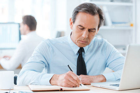 computer writing: Putting his ideas on paper. Serious businessman in formalwear writing in note pad while sitting at his working place