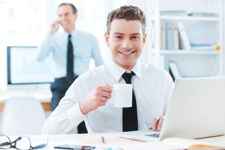 working attire: Business professional.Cheerful businessman in formalwear holding a cup of coffee and smiling at camera while sitting at his desk in office