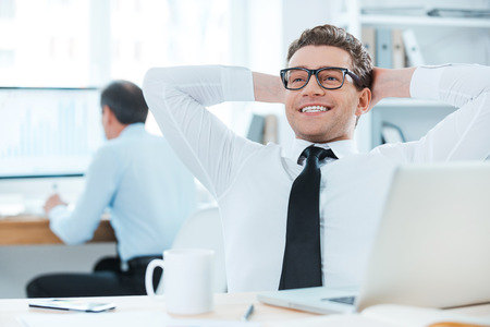 happiness or success: Satisfied with the work done. Cheerful businessman in formalwear holding head in hands while sitting at his desk in the office Stock Photo