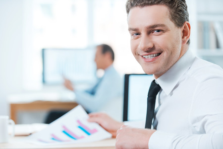 over shoulders: Handsome businessman at work.Happy businessman in formalwear looking over shoulders and smiling at camera while sitting at his desk in office