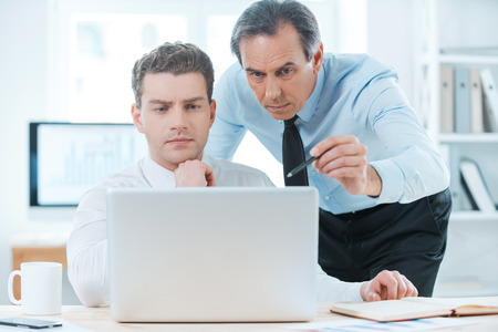同僚と経験を共有します。正装何かを議論し、ノート パソコンを見ての 2 つの深刻なビジネス人々