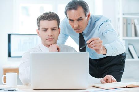 동료와 경험을 공유. 정장 두 심각한 비즈니스 사람들이 뭔가를 논의하고 노트북을 찾고