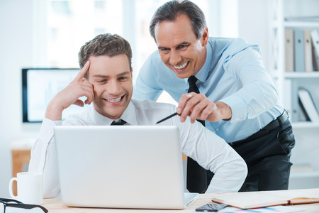 Lending him a hand with his work. Two cheerful business people in formalwear discussing something and looking at laptop