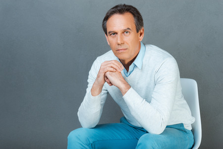 hands clasped: Serious and confident mature man. Thoughtful mature man keeping hands clasped and looking at camera while sitting against grey background