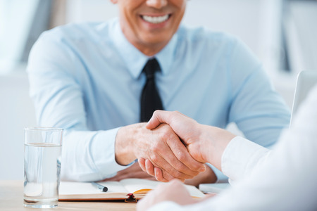 entrevista: Sellado un acuerdo. Primer plano de dos hombres de negocios dándose la mano mientras estaba sentado en el lugar de trabajo