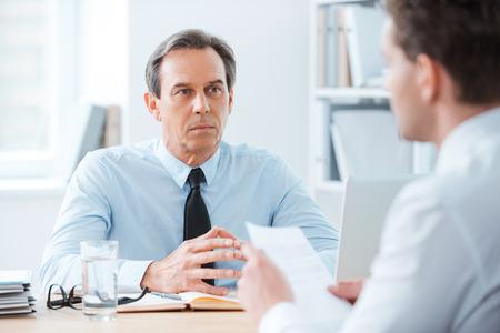dos personas conversando: Reunión de negocios. Dos hombres de negocios sentado en frente de la otra en la oficina mientras se discute algo Foto de archivo