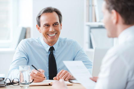 Good job! Two business people sitting in front of each other in the office while discussing something