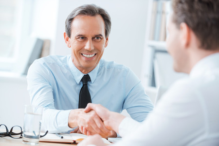 Sealing a deal. Two business people shaking hands while sitting at the working place Stockfoto