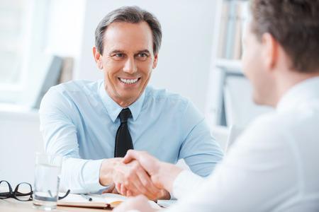 Sellado un acuerdo. Dos hombres de negocios dándose la mano mientras estaba sentado en el lugar de trabajo