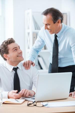 ejecutivo en oficina: Compartiendo buena experiencia. Hombre de negocios alegre sentado en su lugar de trabajo, mientras que su jefe de tocar su hombro y pie cerca Foto de archivo