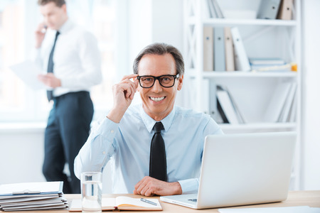 powerful man: Powerful man at his workplace.Happy businessman in formalwear adjusting eyewear and smiling at camera while sitting at his desk in the office Stock Photo
