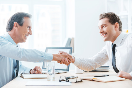 chief: You deserve your success. Side view of two business people shaking hands while sitting at the table in office Stock Photo