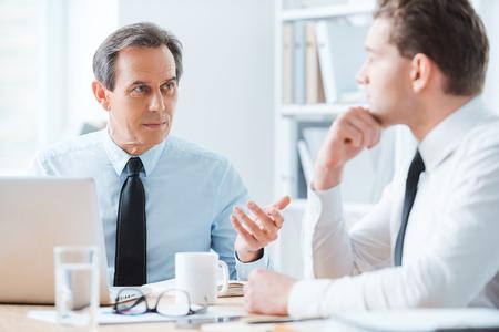 hombre de negocios: Sabio consejo para buen negocio. Dos hombres de negocios en ropa formal hablando de algo mientras estaba sentado en el lugar de trabajo