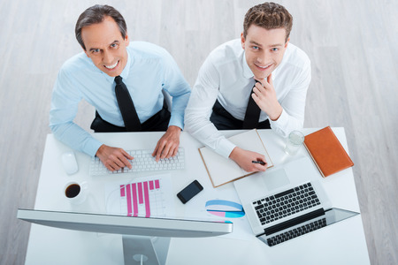 two on top: Business as usual. Top view of two cheerful business people in formalwear working and looking at camera while sitting at working place Stock Photo