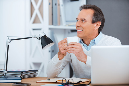 For creation must be inspiration. Thoughtful mature man holding coffee cup while sitting at his working place Stock Photo
