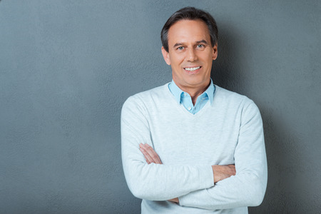 Confident mature man. Confident mature man looking at camera and smiling while keeping arms crossed and standing against grey background Stock Photo