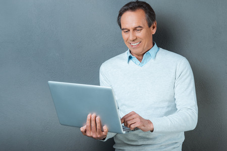 only one senior adult man: Using technology for great advantage. Cheerful mature man working on laptop and smiling while standing against grey background
