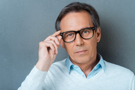 only one senior adult man: Confident mature man. Confident mature man adjusting his eyewear and looking at camera while standing against grey background