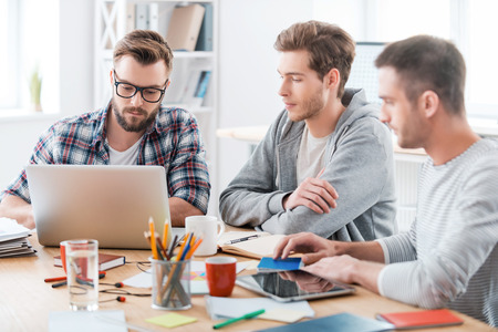 Together they will figure it out. Three young confident men working together while sitting at their working place in office Stock Photo