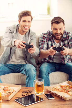 making a face: We love this game! Two cheerful young men playing video games while sitting on sofa