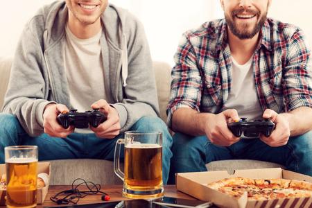 jeu: Temps pour les jeux. Image recadr�e de deux jeunes hommes jouant � des jeux vid�o alors qu'il �tait assis sur le canap�