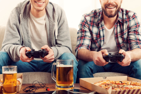 playing video games: Time for games. Cropped image of two young men playing video games while sitting on sofa