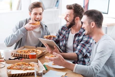 Pizza tijd! Drie jonge vrolijke mannen samen eten pizza tijdens de vergadering in het kantoor Stockfoto