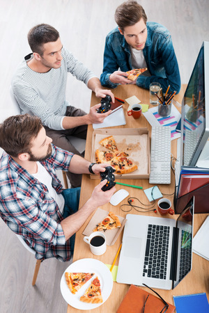 eating pizza: Relaxing after work. Top view of three young men playing computer games and eating pizza while sitting at the desk
