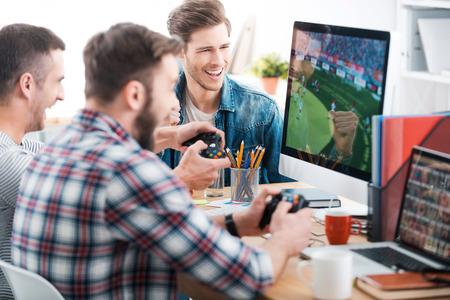 Probando nuevo juego. Tres hombres jóvenes jugando juegos de computadora mientras está sentado en el escritorio en la oficina