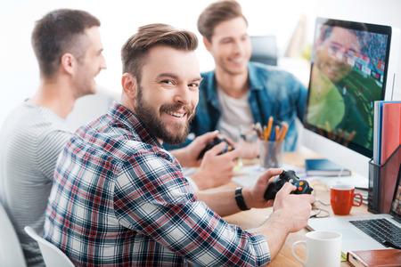 Ciężko pracować, grać ciężko. Trzech młodych mężczyzn grających w gry komputerowe, siedząc przy biurku w biurze