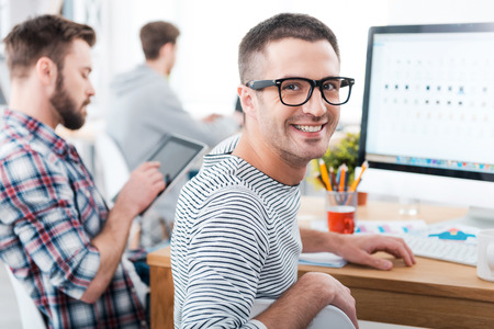 working: We keep it casual in our office. Happy young man looking over shoulder and smiling while sitting at desk with his colleagues working in the background
