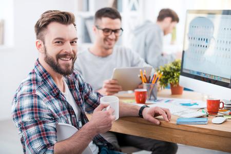 puesto de trabajo: Conseguir el trabajo hecho. Hombre joven hermoso que sostiene una taza de café y sonriendo mientras está sentado en el escritorio en la oficina con sus compañeros de trabajo en segundo plano