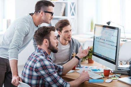 A colaboração é a chave do sucesso. Três executivos novos que discutem algo enquanto olha para o monitor do computador em conjunto