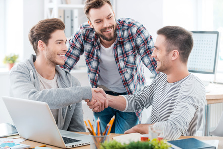 hand job: Good job! Two cheerful young men sitting at the desk and shaking hands while another man standing near and smiling Stock Photo