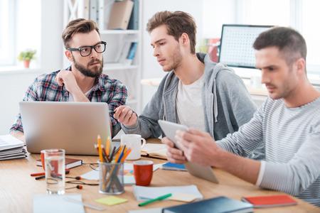 empleado de oficina: Proceso de trabajo. Tres j�venes empresarios que trabajan juntos mientras estaba sentado en su lugar de trabajo en la oficina