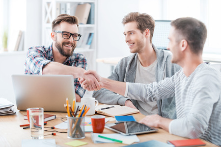 young adult men: Sealing a deal. Business people shaking hands while sitting at the desk in office