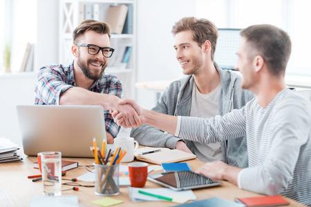 trabajando en computadora: Sellado un acuerdo. La gente de negocios d�ndose la mano mientras est� sentado en el escritorio en la oficina
