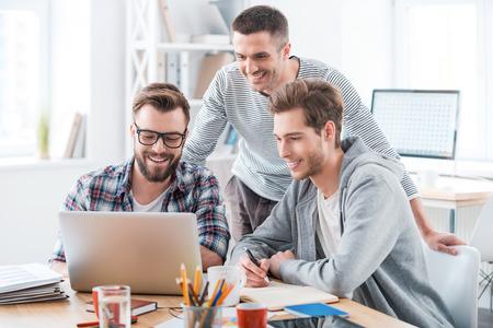 trabajadores: Resoluci�n de problemas como un solo equipo. Tres hombres j�venes alegres que trabajan juntos mientras estaba sentado en su lugar de trabajo en la oficina Foto de archivo