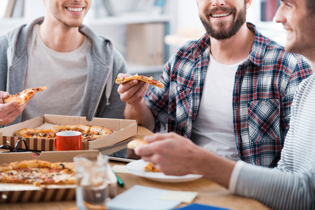 comiendo: Pizza para el trabajo productivo. Recorta la imagen de tres hombres j�venes felices comiendo pizza mientras se est� sentado en el mostrador junto