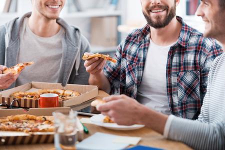 Pizza voor productief werk. Bijgesneden afbeelding van drie gelukkige jonge mannen het eten van pizza's tijdens de vergadering op het bureau samen Stockfoto