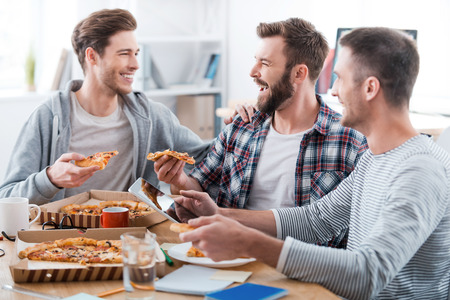 We work hard but have fun doing it! Three happy young men eating pizza together while sitting in the office