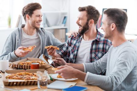 Wir arbeiten hart, aber haben Spaß dabei! Drei glückliche junge Männer, die Pizza isst zusammen, während im Büro sitzen