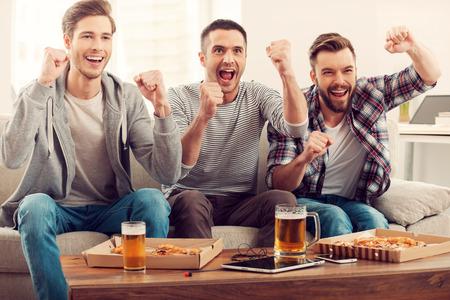 pizza: Ventiladores domésticos. Tres hombres jóvenes felices viendo partido de fútbol y manteniendo los brazos en alto mientras se está sentado en el sofá Foto de archivo
