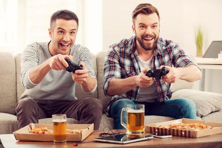 Los jugadores ávidos. Dos hombres felices jóvenes jugando juegos de video mientras se está sentado en el sofá
