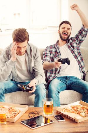 jugando videojuegos: Perdedores y ganadores. Dos jóvenes jugando juegos de video mientras se está sentado en el sofá Foto de archivo